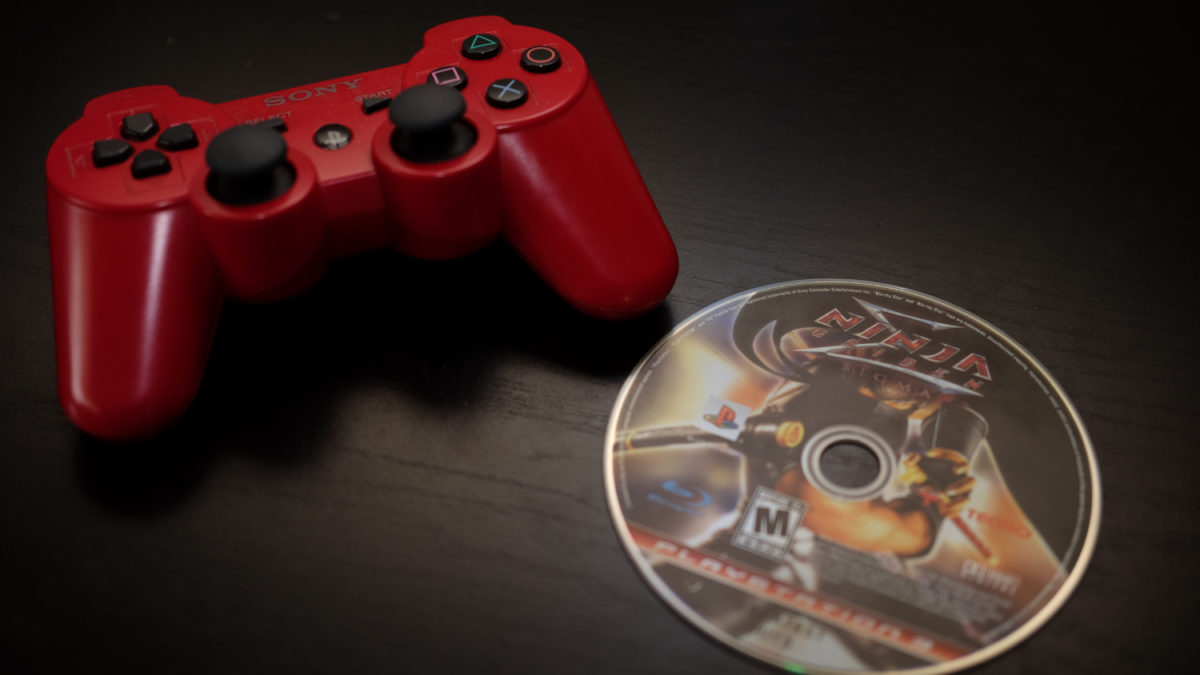 Ninja Gaiden Sigma disc beside red PS3 controller